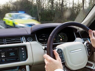 Image supplied by UK Autodrive partners Jaguar Land Rover showing a car receiving an Emergency Vehicle Warning as a police car passes in the oncoming lane.